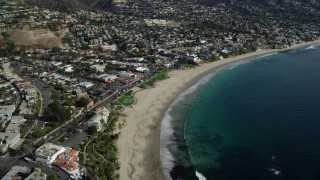 AX0159_220 - 8K stock footage aerial video orbiting Main Beach Park and houses, Laguna Beach, California