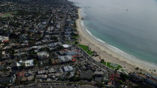 AX0159_221 - 8K stock footage aerial video orbiting business and houses near the beach, Laguna Beach, California
