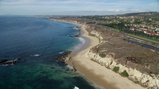 AX0159_229 - 8K stock footage aerial video flying along beach near coastal highway, Newport Beach, California