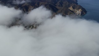 AX0159_250 - 8K stock footage aerial video flying over clouds to reveal Avalon and the harbor on Catalina Island, California