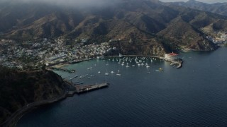 AX0159_257 - 8K stock footage aerial video of a reverse view of boats anchored in Avalon Bay in Avalon, Catalina Island, California