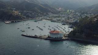 AX0159_262 - 8K stock footage aerial video approaching boats anchored in Avalon Bay harbor by the island town on Santa Catalina Island, California