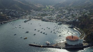 AX0159_263 - 8K stock footage aerial video flying by boats in Avalon Bay harbor and the island town of Avalon on Santa Catalina Island, California