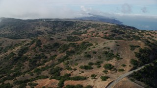 AX0159_270 - 8K stock footage aerial video following a road through the hills toward Catalina Airport, Santa Catalina Island, California