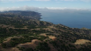 AX0160_001 - 8K stock footage aerial video flying over hills toward the coast of Santa Catalina Island, California