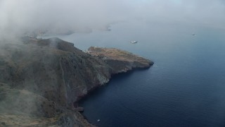 AX0160_006 - 8K stock footage aerial video flying by coastal cliffs to approach the marine science center in Two Harbors, Santa Catalina Island, California