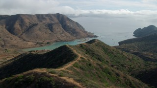 AX0160_012 - 8K stock footage aerial video flying over hills to approach Catalina Harbor in Two Harbors, Santa Catalina Island, California