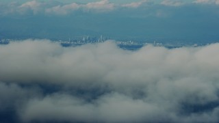 AX0160_026 - 8K stock footage aerial video flying by clouds with a view of Downtown Los Angeles skyline, California