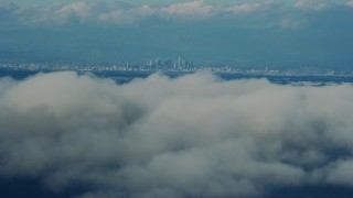 AX0160_027 - 8K stock footage aerial video of Downtown Los Angeles seen from clouds off the coast of California