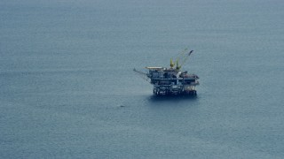 AX0160_034 - 8K stock footage aerial video flying by an oceanic oil rig off the coast of Southern California