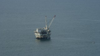 AX0160_038 - 8K stock footage aerial video flying by an oceanic oil derrick off the coast of Southern California