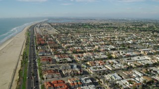 AX0160_043 - 8K stock footage aerial video flying over the beach, Highway 1, and the oceanfront city of Huntington Beach, California