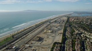 AX0160_044 - 8K stock footage aerial video of homes around an industrial area next to the beach and Hwy 1, Huntington Beach, California