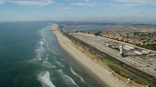 AX0160_045 - 8K stock footage aerial video of Hwy 1 between an industrial area and the beach, Huntington Beach, California