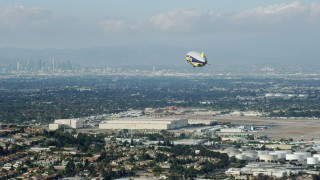 AX0160_061 - 8K stock footage aerial video of the Goodyear Blimp approaching the airport, Downtown LA skyline in background, Long Beach, California