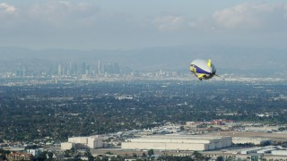 AX0160_062 - 8K stock footage aerial video of the Goodyear Blimp flying toward Downtown Los Angeles skyline from Long Beach Airport, California