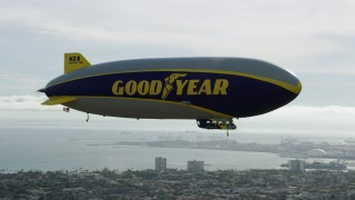 AX0160_065 - 8K stock footage aerial video flying around the Goodyear Blimp over Long Beach, California