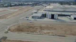 AX0160_067 - 8K stock footage aerial video of a jet making its way to the runway at Long Beach Airport, California
