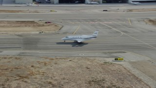AX0160_068 - 8K stock footage aerial video of a private jet taxiing down a runway at Long Beach Airport, California