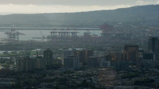 AX0161_003 - 8K stock footage aerial video of cargo cranes at the port and office buildings in Downtown Long Beach, California