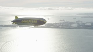 AX0161_005 - 8K stock footage aerial video of the Goodyear Blimp flying by Downtown Long Beach, California
