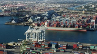 AX0161_009 - 8K stock footage aerial video of cranes loading containers onto a ship at the Port of Long Beach, California