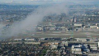AX0161_044 - 8K stock footage aerial video approaching the airport, partially obscured by low level clouds, LAX, California