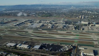 AX0161_045 - 8K stock footage aerial video approaching the airport as airlines taxi on the runways, LAX, California
