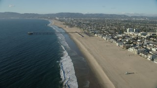 AX0161_060 - 8K stock footage aerial video flying over the beach toward the Venice Fishing Pier in Venice, California