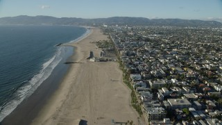 AX0161_061 - 8K stock footage aerial video flying over the beach end of the Venice Fishing Pier and Venice Beach in Venice, California