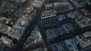 AX0161_115 - 8K stock footage aerial video orbiting office buildings on Camden Drive to reveal shops on Rodeo Drive in Beverly Hills, California