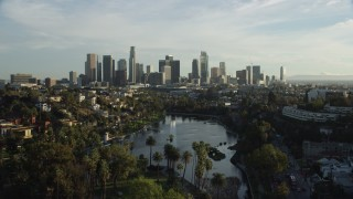AX0162_001 - 8K stock footage aerial video flying over Echo Park Lake to approach the skyline in Downtown Los Angeles, California
