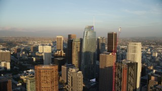 AX0162_071 - 8K stock footage aerial video flying by Wilshire Grand Center and skyscrapers at sunset in Downtown Los Angeles, California