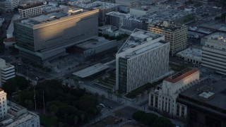 AX0162_076 - 8K stock footage aerial video orbiting LAPD headquarters at twilight in Downtown Los Angeles, California, and reveal city hall