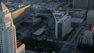 AX0162_077 - 8K stock footage aerial video orbiting city hall to approach LAPD headquarters at twilight in Downtown Los Angeles, California