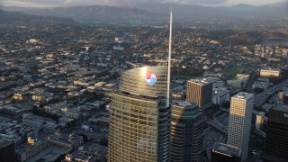AX0162_080 - 8K stock footage aerial video orbiting the top of Wilshire Grand Center at sunset in Downtown Los Angeles, California