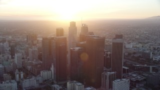 AX0162_085 - 8K stock footage aerial video of a reverse view of the tall towers of downtown at sunset in Downtown Los Angeles, California