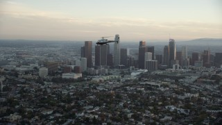 AX0162_092 - 8K stock footage aerial video tracking an LAPD helicopter flying by the skyline of Downtown Los Angeles, California at twilight
