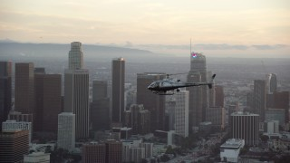 AX0162_094 - 8K stock footage aerial video LAPD helicopter flying by Downtown Los Angeles, California at twilight
