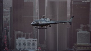 AX0162_095 - 8K stock footage aerial video tracking an LAPD helicopter flying by Downtown Los Angeles, California at twilight