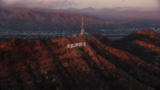 AX0162_102 - 8K stock footage aerial video flying by the famous Hollywood Sign at twilight in Los Angeles, California