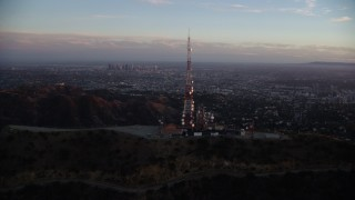 AX0162_103 - 8K stock footage aerial video orbiting the Hollywood Sign at twilight to reveal Downtown Los Angeles, California