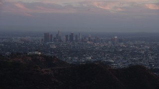 AX0162_105 - 8K stock footage aerial video of Downtown Los Angeles, California at twilight, reveal Griffith Observatory