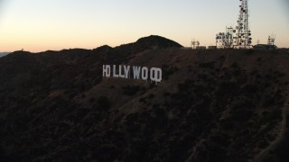 AX0162_108 - 8K stock footage aerial video approaching and flying by the famous Hollywood Sign at twilight in Los Angeles, California