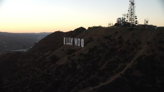 AX0162_109 - 8K stock footage aerial video flying by the famous Hollywood Sign to reveal setting sun in Los Angeles, California