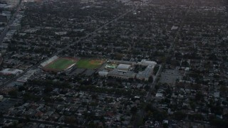 AX0162_112 - 8K stock footage aerial video flying away from John Burroughs High School at twilight in Burbank, California
