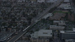 AX0162_113 - 8K stock footage aerial video of a Metrolink commuter train passing neighborhoods at twilight in Burbank, California