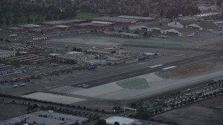 AX0162_114 - 8K stock footage aerial video orbiting the end of a runway and terminals at twilight at Burbank Airport, California