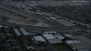 AX0162_115 - 8K stock footage aerial video of commercial airplanes on the end of the runway at Burbank Airport, California, twilight
