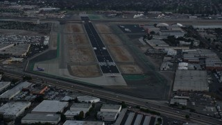 AX0162_116 - 8K stock footage aerial video of a commercial airplane starting down the runway at Burbank Airport, California, twilight